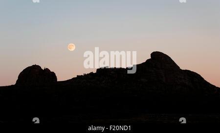 Full moon rising over silhouette of Haytor, Dartmoor, Devon - Stock Photo