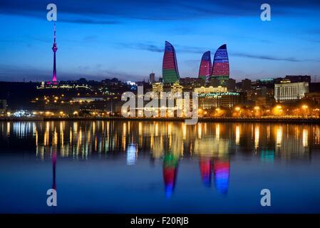 Azerbaijan, Baku, Baku Bulvar (Boulevard), city illuminated at dusk reflected in the Caspian sea, the Flame Towers - Stock Photo