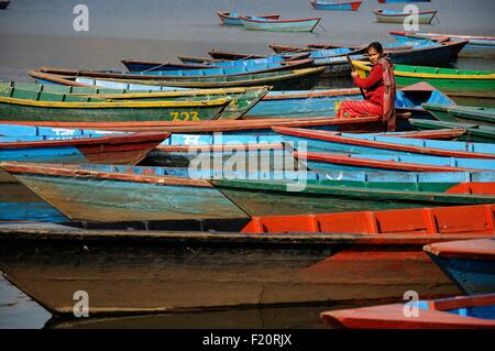 Nepal, Pokhara, woman in red among the colourful wooden boats on th lake Phewa Tal - Stock Photo