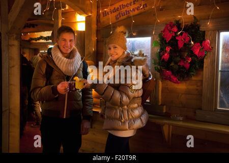 Austria, Upper Austria, Linz, Christmas, young couple enjoying a hotwine (glⁿhwein) in the Volksgarten Christmas - Stock Photo
