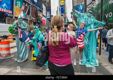 United States, New York City, Times Square, Statue-of-Liberty-dressed actors posing with tourists - Stock Photo