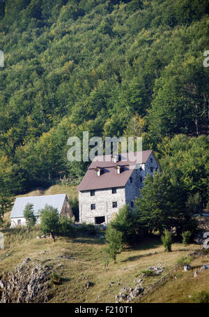 new building in the Albania village of Lepushe with a forested mountain slope behind it