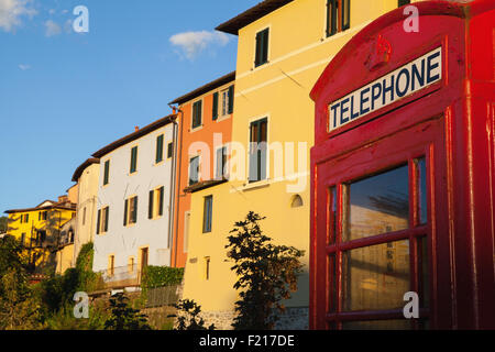 Italy, Tuscany, Lucca, Barga, British telephone box with facades of old town houses in the background. - Stock Photo