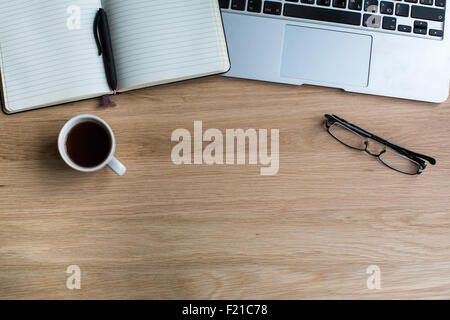 Notepad with pen, keyboard, glasses and Cup of coffee on a wooden table texture. Top view with space for text. - Stock Photo