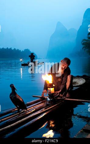 Chinese cormorant fisherman lights his lantern at dawn, Li River, Xingping, China, Asia - Stock Photo