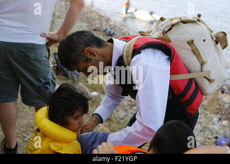 Lesbos, Greece. 9th September 2015. A father removes the life jacket from his child on the beach of Lesbos. Hundreds - Stock Photo