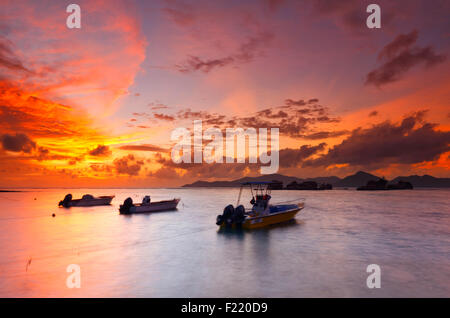 Colorful sunset on Seychelles with a beautiful clouds. Island La Digue. - Stock Photo
