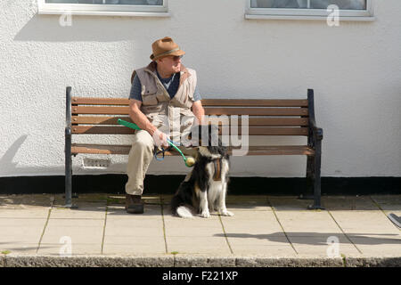 Man and border collie dog sat on wooden bench waiting for wife who is shopping in Stony Stratford, Buckinghamshire, - Stock Photo