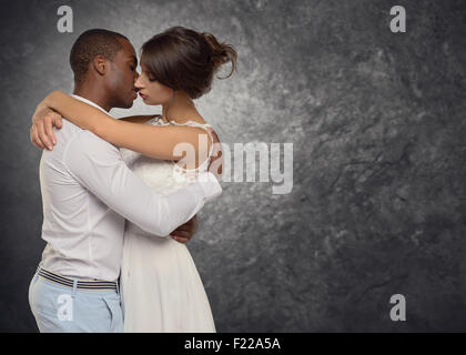 Young couple deeply in love hugging and kissing passionately in a tender moment, side view upper body of a multiracial - Stock Photo