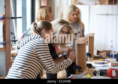 Middle aged people attending a Do-It-Yourself course learning basic carpentry skills, UK - Stock Photo