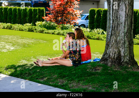 Two college girls enjoying the summer sunshine and ice creams in Coeur d'Alene Idaho - Stock Photo