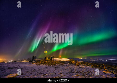 People enjoying the Aurora Borealis or Northern lights on Mt. Ulfarsfell, near Reykjavik,  Iceland. The Hellisheidi - Stock Photo