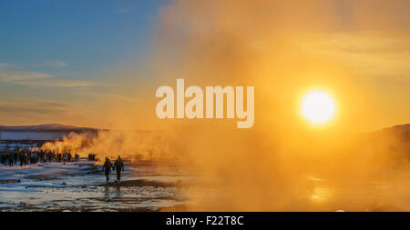 Tourist by the steam rising at Geysir, a popular tourist attaction, Iceland. - Stock Photo