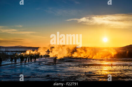 Tourist by the steam rising at Geysir, a popular tourist attraction, Iceland. - Stock Photo