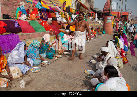 A Pandit (holy man and priest who performs ceremonies) conducts puja (prayer) with  pilgrims on the ghats at Varanasi - Stock Photo