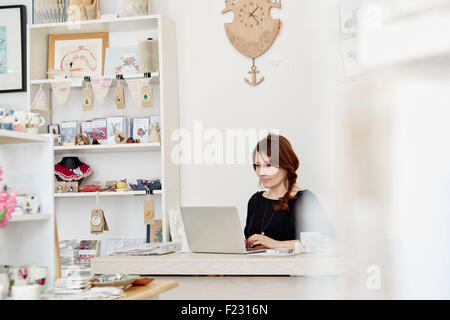 A woman sitting at a desk in a small gift shop, doing the paperwork, managing the business, using a laptop. - Stock Photo