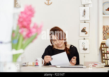 A woman sitting at a desk in a small gift shop, doing the paperwork, managing the business. A laptop on the desk. - Stock Photo