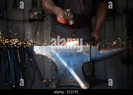 A blacksmith shaping a hot piece of iron on an anvil with a hammer, with sparks flying. - Stock Photo
