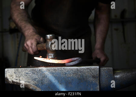 A blacksmith shaping a hot piece of iron on an anvil using a hammer. - Stock Photo