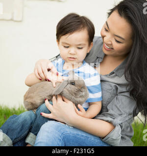 Smiling woman holding a rabbit, her young son sitting on her lap, stroking the animal. - Stock Photo