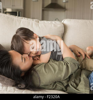 A woman lying on a sofa, smiling, cuddling her young son. - Stock Photo