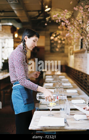 A woman wearing an apron pouring water into glasses on table in a restaurant. - Stock Photo