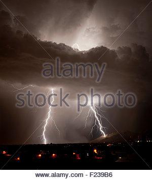 A huge lightning bolt strikes the side of the Santa Catalina Mountains near Pusch Ridge at night summer monsoon - Stock Photo