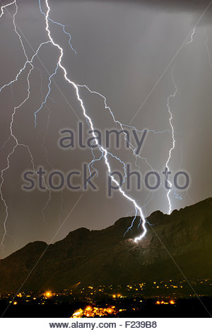 A huge lightning bolt strikes the side of the Santa Catalina Mountains near Pusch Ridge at night a summer monsoon - Stock Photo