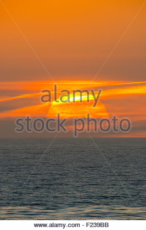Sunset over the Pacific Ocean from La Jolla California of the huge setting sun over the sea - Stock Photo