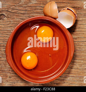 high-angle shot of an earthenware plate with some cracked chicken eggs on a rustic wooden table - Stock Photo