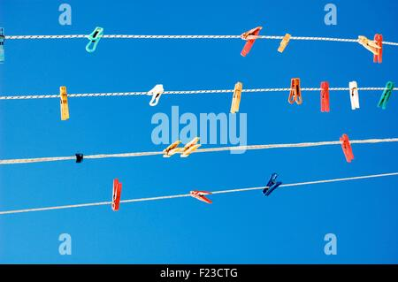 Multicolored pegs on washing lines against a bright blue sky - Stock Photo
