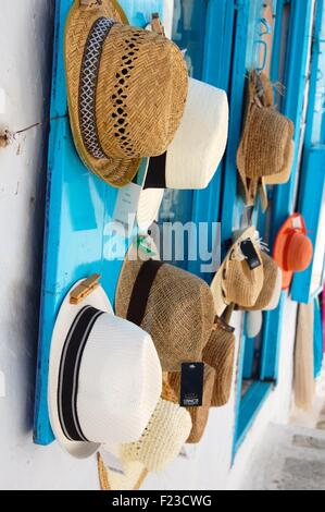 Hats hanging outside a shop in Chora, Amorgos Greece - Stock Photo