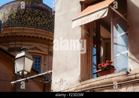 A flower pot sits in a window at the Hotel L'Abbaye with the dome of the Nice Cathedral in the background. - Stock Photo