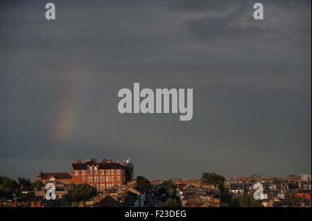 A rainbow over terraced houses in London with a grand building in the background - Stock Photo
