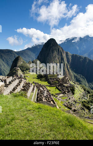 Peru, Morning sun lights Inca ruins at Machu Picchu with Huayna Picchu peak rising above the Urubamba River - Stock Photo