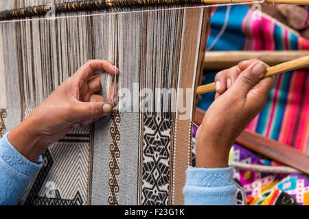 Peru, Cusco Region, Woman weaving using traditional loom outside gift shop at Ccochahuasi Animal Sanctuary in Sacred - Stock Photo