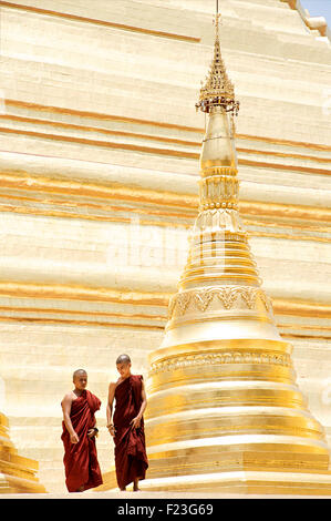 Monks standing beside stupa of Shwedagon Pagoda, Rangoon, Burma - Stock Photo