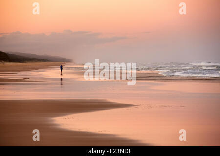 Lone fisherman, on Seventy Five Mile Beach, Fraser Island, Queensland, Australia. Fraser Island is the largest sand island in th