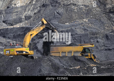 WESTPORT, NEW ZEALAND,AUGUST 31, 2013: A 40 ton digger loads coal into a truck at Stockton open cast coal mine - Stock Photo