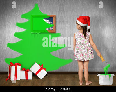 Funny child dressed Santa hat, draws Christmas tree on wall at home, xmas concept - Stock Photo