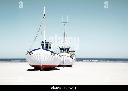 Fishing boats lying in the sand, on the beach, Jutland, Denmark - Stock Photo
