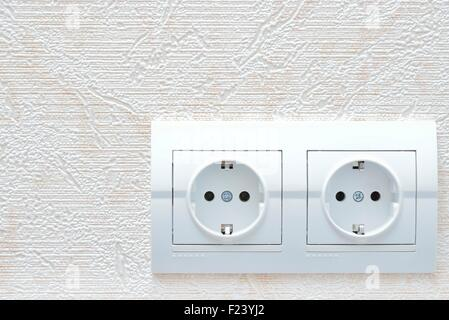 two white new electrical sockets (rosette) on wall - Stock Photo