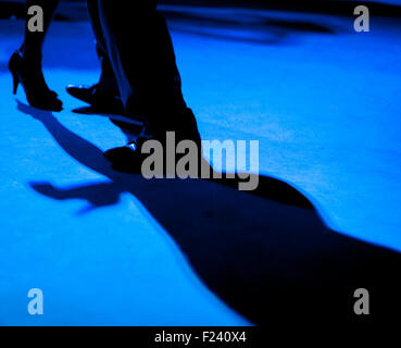Detail of shoes with shadows in milonga ballroom. - Stock Photo
