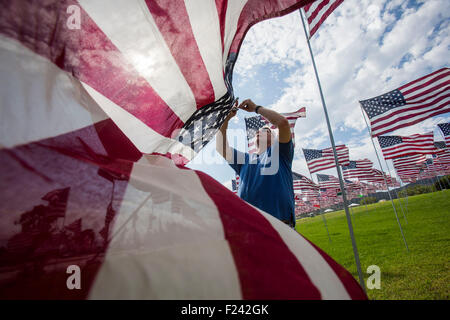 Los Angeles, California, USA. 10th Sep, 2015. A man erects a US flag to honor the victims of the September 11, 2001 - Stock Photo