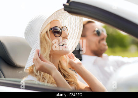 happy man and woman driving in cabriolet car - Stock Photo