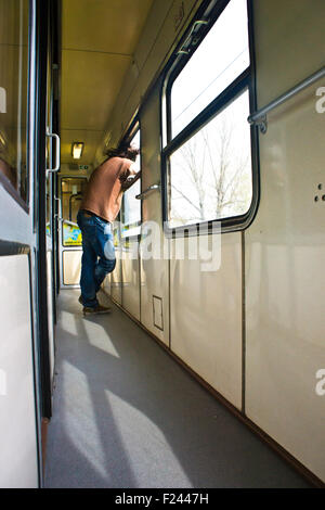 boy in train corridor looking out of the window - Stock Photo