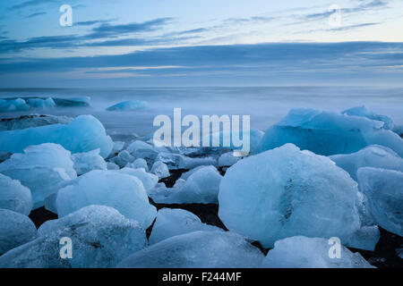 Icebergs from the Jokulsarlon glacial lagoon washed up on a black volcanic sand beach. South Iceland. - Stock Photo