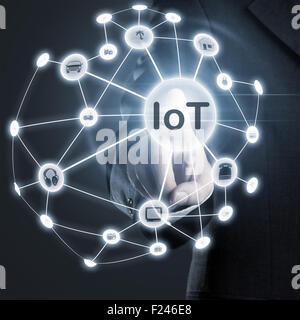 Man touching IoT (internet of things) network on display - Stock Photo