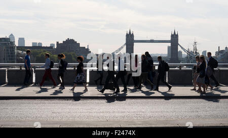 crowd of commuters and office workers crossing London Bridge on way to work during rush hour, with Tower Bridge, - Stock Photo