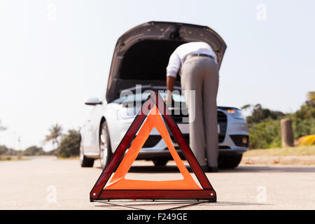 driver trying to figure out how to fix broken down car with red triangle to warn other road users - Stock Photo